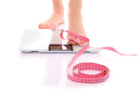 A picture of female feet standing on a bathroom scales and a tape measure over white background photo