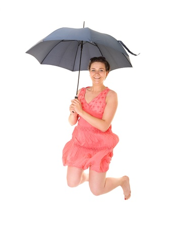 A picture of a young positive woman jumping with an umbrella and smiling over white background Stock Photo - 14394472