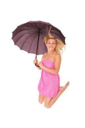 A picture of a young positive woman jumping with an umbrella and smiling over white background Stock Photo - 14394383