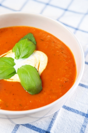A picture of a white bowl full of fresh tomato soup with basil leaves on top photo
