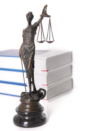 A picture of a Themis statue standing in front of code books over white background photo