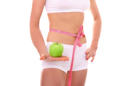 A picture of a fit woman standing over white background with a green apple and tied with a tape measure Stock Photo - 14735851