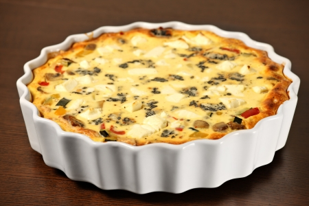 A picture of freshly baked vegetable quiche in a white tin over wooden surface photo