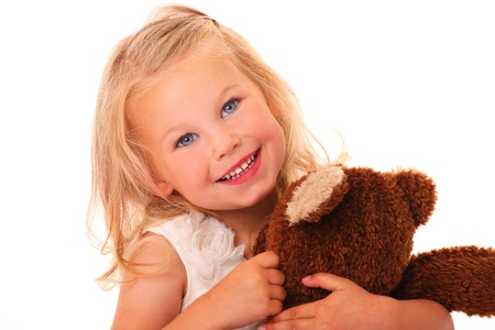 A portrait of a young pretty girl smiling and hugging her teddy bear over white background photo