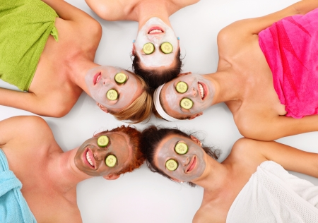 spa: A picture of five girl friends relaxing with facial masks on over white background