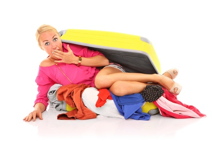 A picture of a young sexy woman trying to pack herself into the suitcase over white background Stock Photo - 16660997