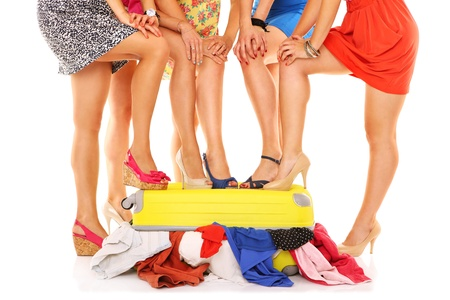 packing suitcase: A picture of five women with their sexy legs put on a suitcase over white background Stock Photo