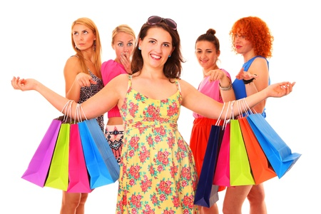 A picture of a young pretty woman with shopping bags and her jealous friends in the back over white background photo
