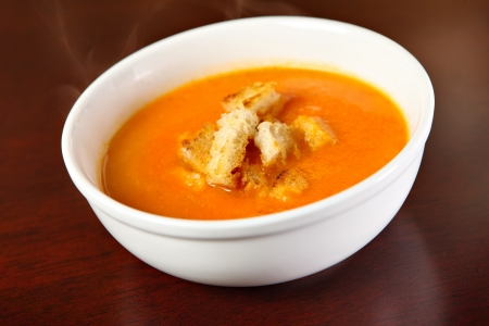 tomato soup: A bowl of red pepper cream soup served on a wooden surface