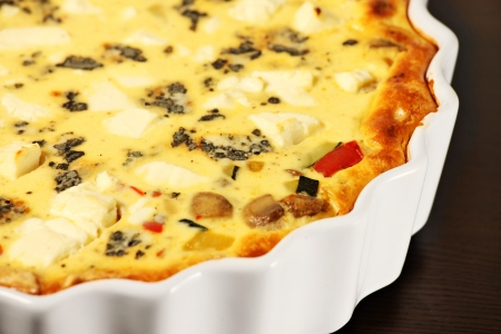 A picture of freshly baked vegetable tart in a white tin over wooden surface photo