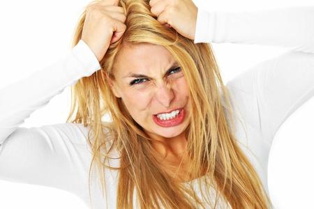 mujer enojada: Una imagen de una mujer joven deprimida arrancando el cabello sobre fondo blanco Foto de archivo