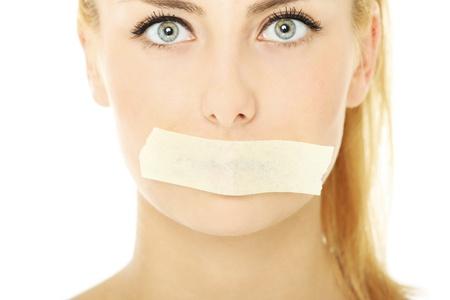 cintas: Una imagen de una mujer joven con una cinta adhesiva en la boca sobre fondo blanco