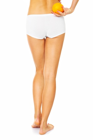 A picture of the back of female legs and an orange over white background Stock Photo - 17573245