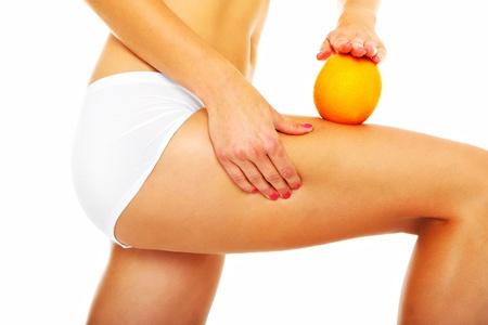 A picture of female legs and an orange over white background photo
