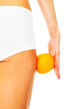 A picture of female legs and an orange over white background Stock Photo - 17573288