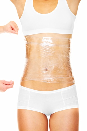 digesting: A picture of a sexy female body being wrapped around with foil to reduce fat over white background