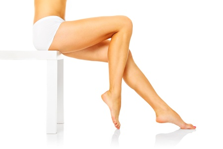 girl feet: A picture of a sexy woman sitting over white background and showing her legs