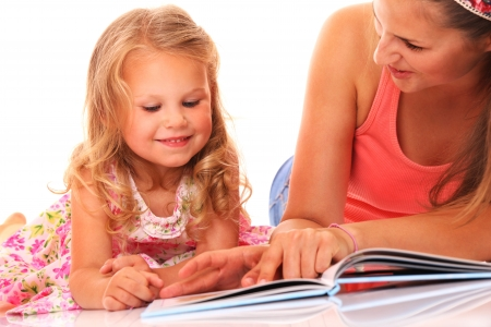 A portrait of a mother and daughter reading a book over white background photo
