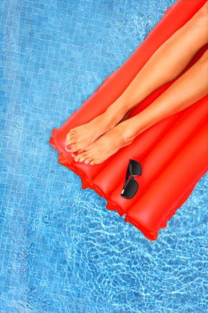 A picture of female legs lying on a red inflatable mattress over blue water photo