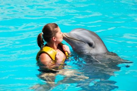 Una imagen de una mujer joven que besa a un delfín en un agua turquesa Foto de archivo