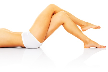 A picture of a sexy woman lying over white background and showing her legs photo
