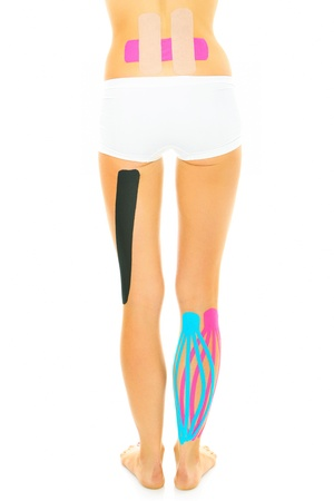 A picture of the back of a woman with physio tape on different parts of her body over white background photo
