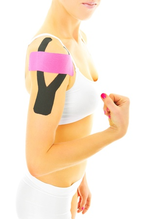 A picture of a special physio tape put on an injured arm muscles over white background photo