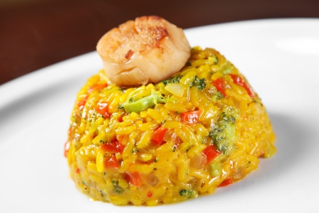 kitchen spanish: A picture of a fresh portion of paella with scallops served on a white plate Stock Photo