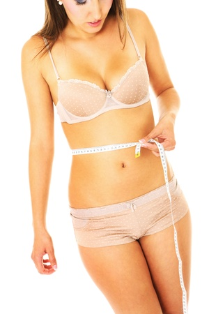 A picture of a young fit woman checking her measurements over white background photo