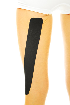 A picture of a special physio tape put on an injured leg muscle over white background photo