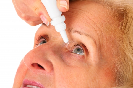 A picture of an elderly woman applying eyedrops over white background photo