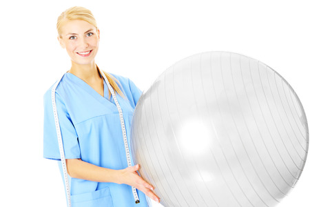 A picture of a young physiotherapist holding a ball over white background photo