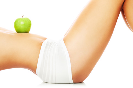 flat stomach: Una imagen de una mujer sosteniendo una manzana verde en su vientre en forma