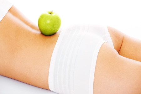 green back: A picture of a fit woman with a green apple on her back  lying over white background Stock Photo