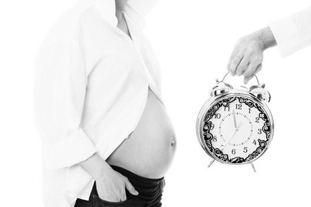 A black and white picture of a pregnant woman and a clock over white background photo