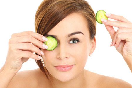 A picture of a face of a beautiful woman posing with a cucumber over white background photo