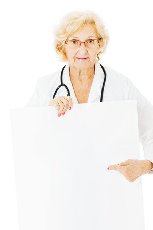 Portrait of senior female doctor pointing at blank billboard isolated over white background photo