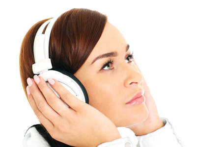 whie: A picture of a young woman listening to music over whie background Stock Photo