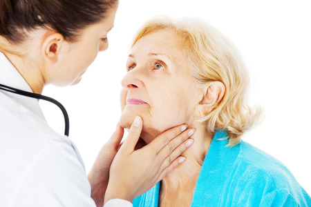 Young female doctor examining senior womans throat isolated over white background