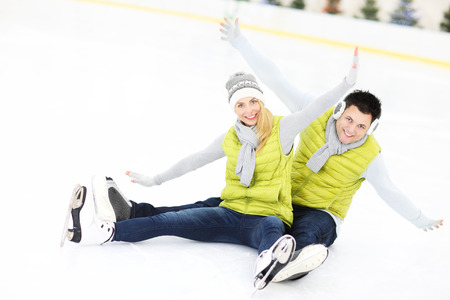 ice skating: A picture of a young couple resting on an ice rink