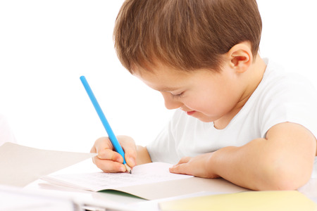 A picture of a little boy doing homework over white background Imagens