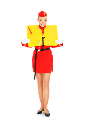 A picture of an attractive stewardess presenting a life vest over white background 版權商用圖片