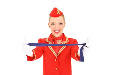 hotesse de l air: Une image d'une hôtesse de l'air attrayant présentant une fixation de ceinture de sécurité sur fond blanc Banque d'images
