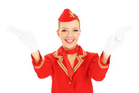 salidas de emergencia: Una foto de una azafata atractiva que muestra las salidas de emergencia más de fondo blanco Foto de archivo