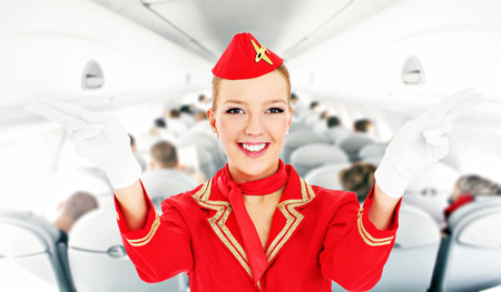 salidas de emergencia: Una foto de una azafata atractiva que muestra las salidas de emergencia en un avión Foto de archivo