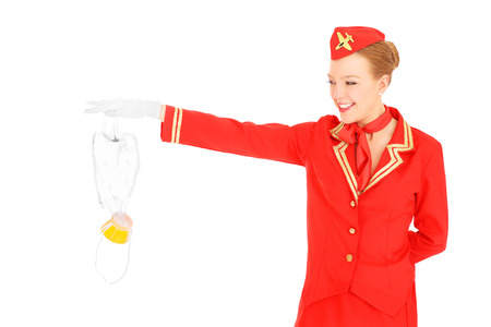 A picture of an attractive stewardess presenting an oxygen mask over white background Фото со стока