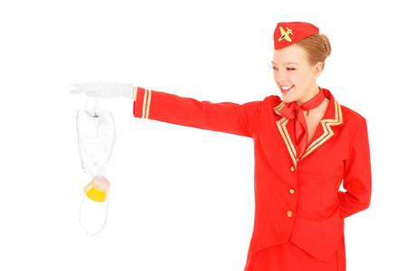 Een foto van een aantrekkelijke stewardess presentatie van een zuurstofmasker op een witte achtergrond