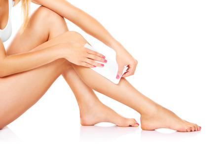 A picture of a young woman waxing her legs over white background photo