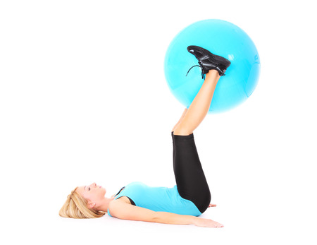 A picture of a beautiful young fit woman exercising with a ball over white background photo