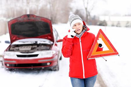 Een beeld van een jonge vrouw die een probleem met een auto op een winter weg